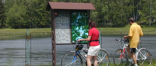 Cyclist in front of an information board